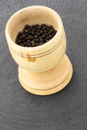 morter: handmade wood mortar full with aromatic black peppercorns Stock Photo