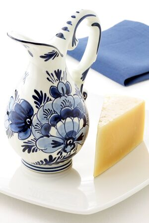 delftware: dutch antique glazed blue and white delftware jar, full of fresh milk with gouda cheese Stock Photo