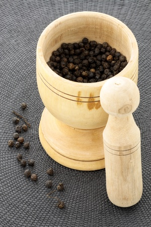 morter: wood mortar and pestle full with aromatic black peppercorns