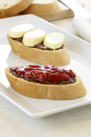 delicious fresh hazelnut and chocolate spread sandwich with fresh strawberries jelly or jam and sliced bananas photo