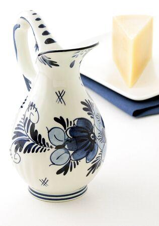 delftware: olandese antico vaso smaltato blu e bianco delftware, piena di latte fresco con formaggio Gouda
