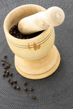 wood mortar and pestle full with aromatic black peppercorns Stock Photo - 12054742