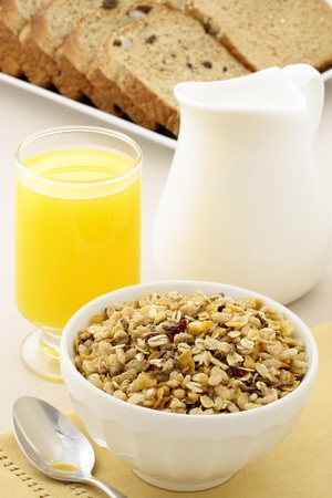 delicious breakfast with orange juice, whole grain bread,milk and a healthy bowl of cereal. photo