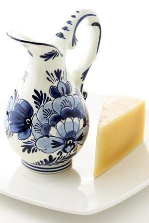 delftware: olandese antico vaso smaltato blu e bianco delftware, pieno di latte fresco con formaggio gouda Archivio Fotografico