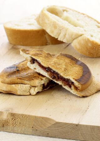 delicious rustic warm fresh hazelnut and chocolate spread sandwich with strawberries jelly or jam photo