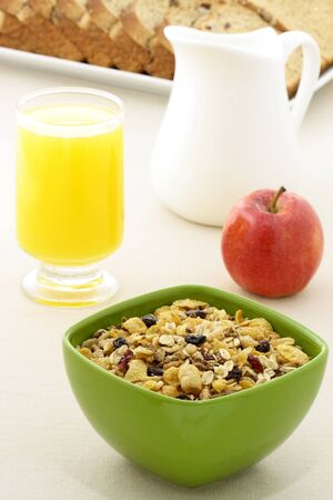 delicious breakfast with whole grain bread,fresh red apple and a healthy bowl of muesli cereal. photo
