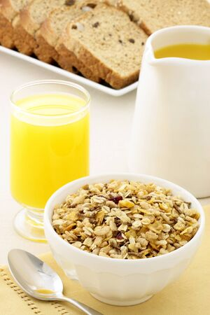 delicious breakfast with orange juice, whole grain bread and a healthy bowl of muesli cereal  photo