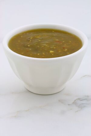 Artisan mexican tomatillo sauce on retro vintage carrara marble setting, with a spicey mild hot flavor perfect for all your Mexican, tex-mex recipes and sides.