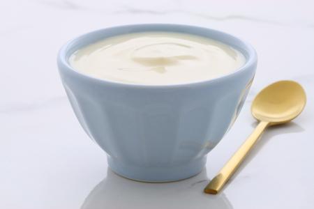 Delicious, nutritious and healthy fresh plain yogurt on vintage italian carrara marble setting.