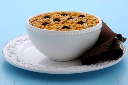 Delicious and nutritious lightly toasted breakfast muesli or granola cereal on vintage styling. Stock Photo
