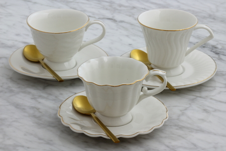 trendy and beautiful antique porcelain tea cups styled on carrara marble table Imagens
