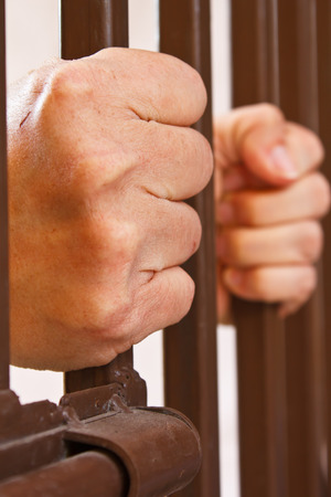 waiting convict: hands behind bars in jail or prison  Stock Photo