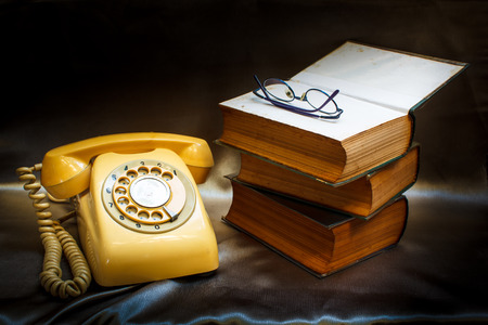 ancient telephone: retro phone and book in vintage style.