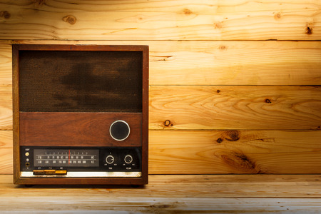 radio frequency: old retro radio with light on wood table.