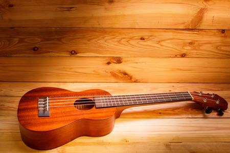 horizontals: Ukulele on pallet wood background and beautiful light.