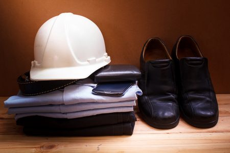 workwear, boots and wallet and mobile on wooden table. photo