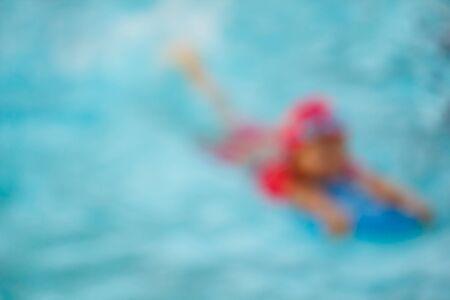 kiddies: blur of children in the pool, background.
