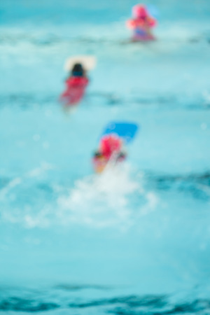 kiddies: blur of children in the pool, background.