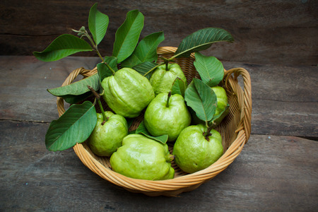Fresh green guavas on old wood background. Banco de Imagens