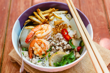 Bowl of noodles with shrimp and pork on wooden table.