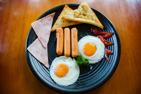 eggs and bacon: Breakfast with fried eggs, bacon, sausages and toasts.