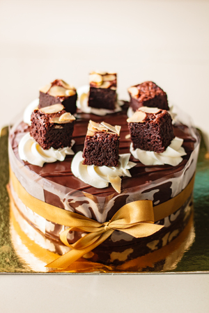 Chocolate cake with fudge sauce, decoration with brownies. Stock Photo