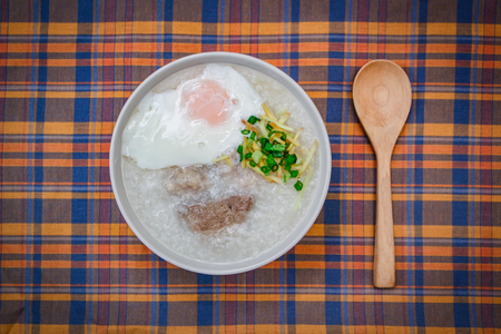 Rice porridge with soft boiled egg, ginger and chopped spring onion, thai style.