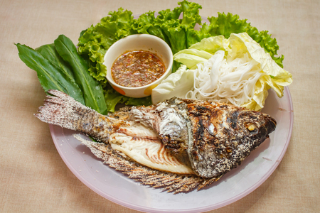 Salt-Crusted Grilled Fish and mix vegetable on plate, thai food.