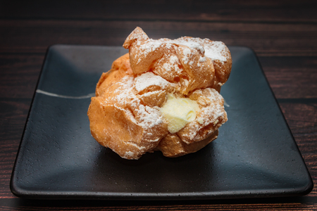 Choux Cream filled vanilla custard and dusted with icing on a plate. Banco de Imagens