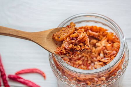 Pork crackling chili paste with the ingredient on wood background.