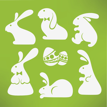 rabbit ears: white Easter rabbits silhouettes on green background