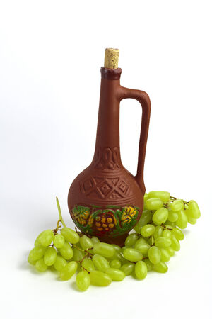 clay bottle and grapes on a white background photo