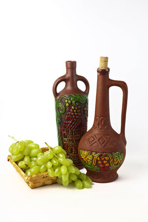 clay bottles and grapes on a white background photo