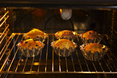 Baking cupcakes with raisins in baskets are baked in the oven photo
