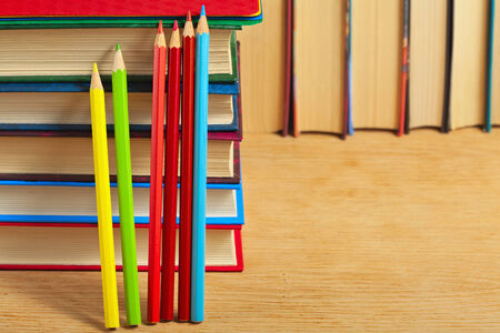 books on a wooden surface: Pile of books and colored pencils on a wooden surface