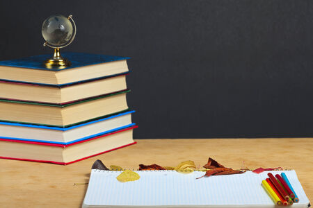 Notebook with colored pencils and autumn leaves on a wooden surface. photo