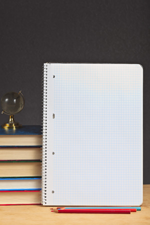 Notebook with colored pencils and pile of books on a wooden surface. photo
