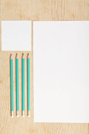 blanks: Blanks of empty paper with pencils on a wooden surface. Stock Photo