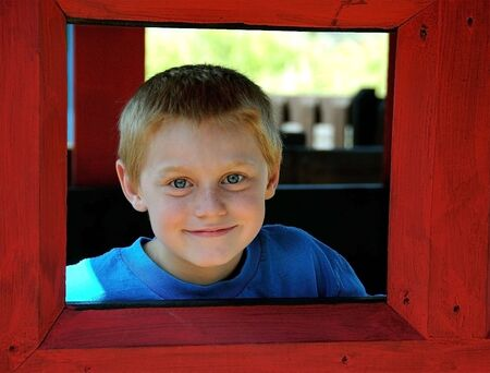 A cute young boy enjoys the park while posing for photographs on a summer day.
