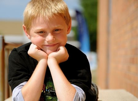 A cute young boy is posing for photographs on a summer day.