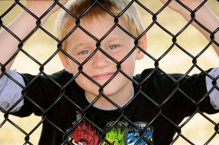 A cute young boy enjoys poses for a photograph behind a fence on a summer day.