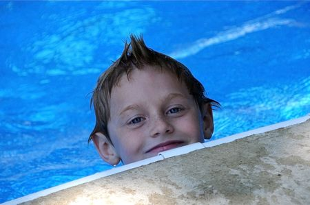 A young boy enjoys playing in the pool on a summer day.