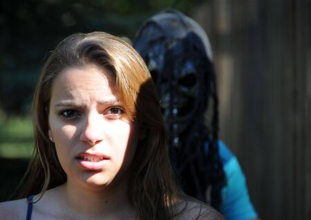 A girl stands with scared look while a man stands behind her with a scary mask.