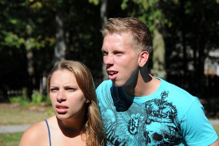 Male and female siblings are looking at something with surprise.