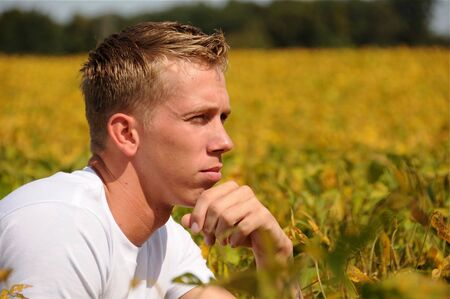 An adult male enjoys a warm summer day, looking out over a field of crops. 写真素材