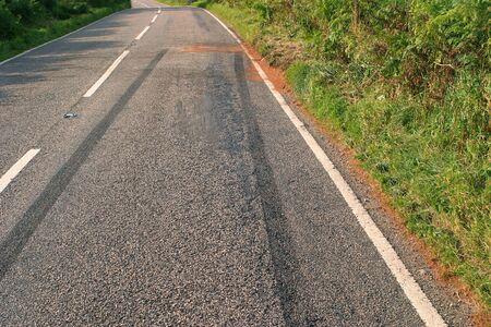 skid: Skid marks left in the road after a car crash on a rural road.
