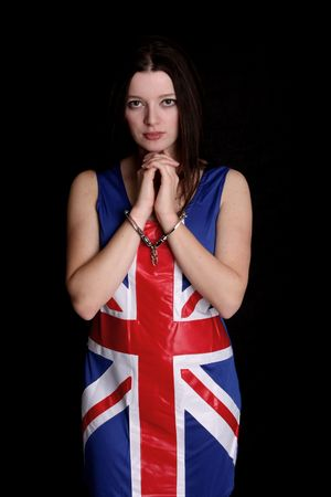 model in a Union Jack dress in a pair of handcuffs isoltaed on black Stock Photo