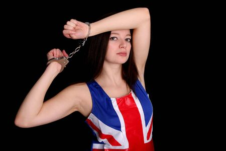 woman handcuffs: fashion model posing in a Union Jack dress, wearing a pair of handcuffs