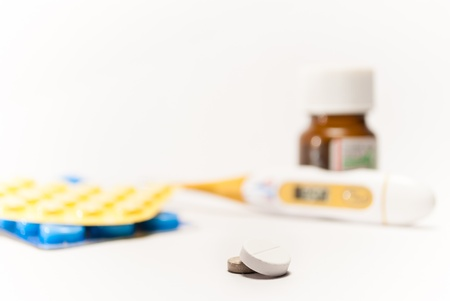 medicines in the foreground with thermometer and strips in the background photo