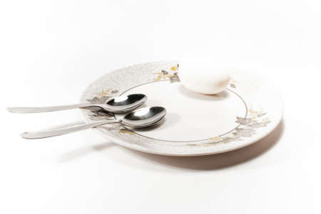 eggcup: A plate, two spoons and an egg Stock Photo